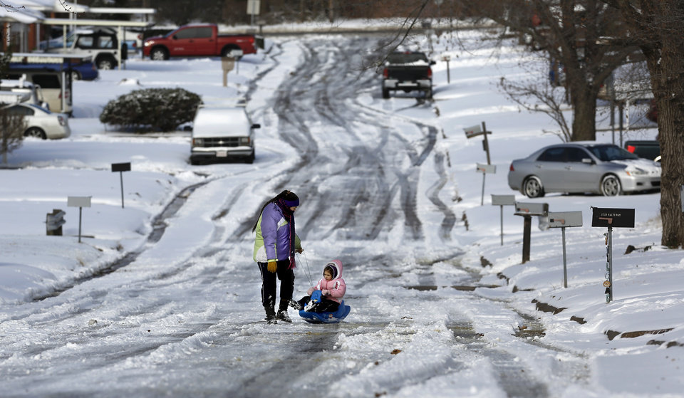Sarah Stefanoff, 4, rides on a sled pulled by her older sister, Dessi Stefanov, 14 on Waltz Way  in Midwest City on Friday, Dec. 6, 2013.  NOTE: The girls are sisters, but they have different spellings of their last names. The spellings are correct. Photo by Jim Beckel, The Oklahoman