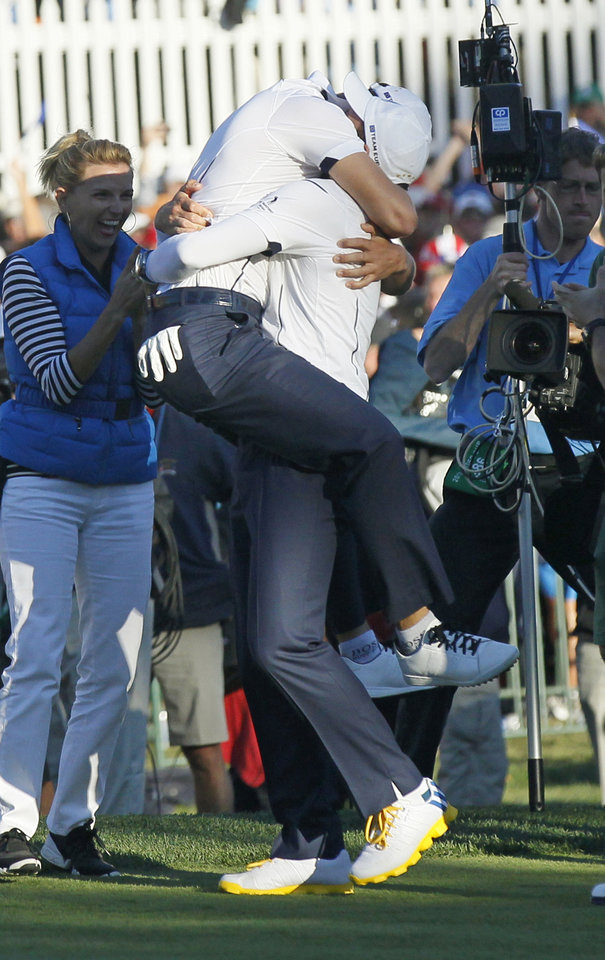 Europe's Martin Kaymer leaps into the arms of Sergio Garcia after winning the Ryder Cup PGA golf tournament Sunday, Sept. 30, 2012, at the Medinah Country Club in Medinah, Ill. (AP Photo/Charles Rex Arbogast)  ORG XMIT: PGA200