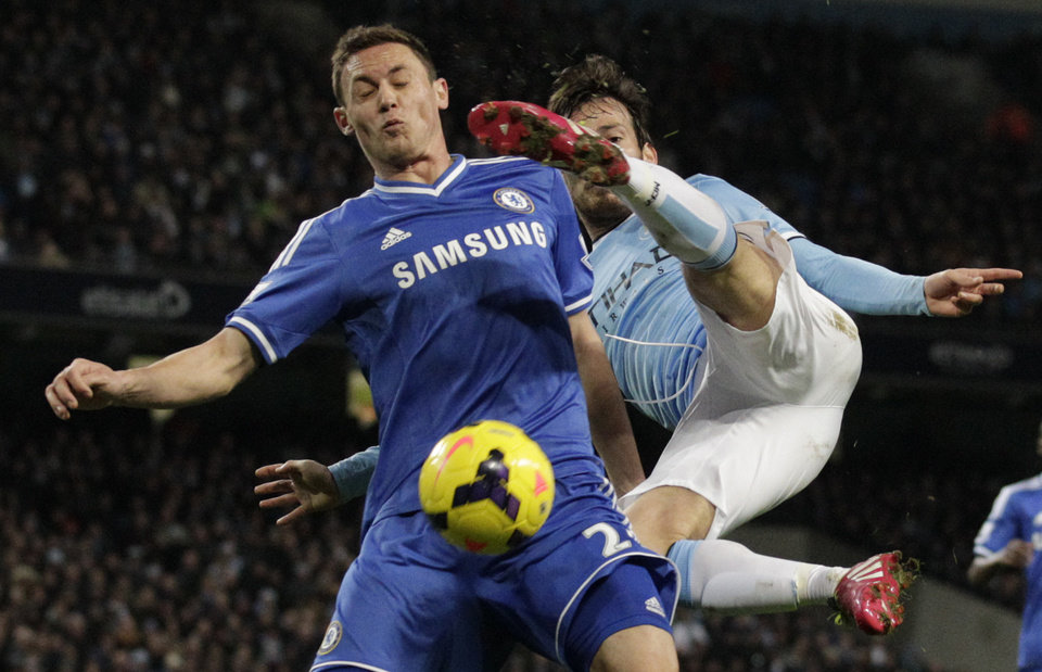 Photo - Manchester City's David Silva, right, attempts an airborne shot on goal under pressure from Chelsea's Nemanja Matic during their English Premier League soccer match at the Etihad Stadium, Manchester, England, Monday, Feb. 3, 2014. (AP Photo/Jon Super)
