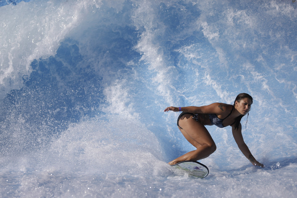 Sammantha Aker, of Huntington Beach, Calif., rides the machine-made wave at Wavehouse San Diego, Wednesday, Sept. 18, 2013, in San Diego. Surf parks - massive pools with repeating, artificial waves - are the latest buzzword in the surf community, as everyone from top athletes to retailers look for ways to expand the sport, boost surf-related sales and create a standardized way to train that could ultimately help surfing earn an Olympic pedigree. (AP Photo/Gregory Bull)