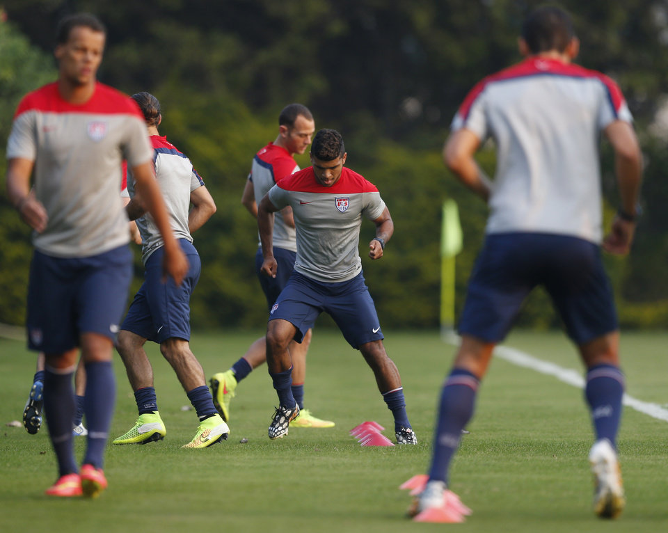 Photo - United States' DeAndre Yedlin, center, works out with teammates during a training session in Sao Paulo, Brazil, Tuesday, June 17, 2014.  The United States will play against Portugal in group G of the 2014 soccer World Cup on June 22. (AP Photo/Julio Cortez)