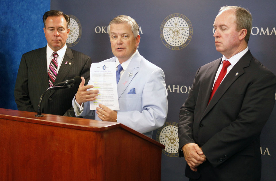 Photo - Insurance Commissioner John Doak speaks to members of the media along with Rep. Todd Russ left, and Rep. Marty Quinn, as they unveil insurance legislation during a news conference at the state Capitol in Oklahoma City on Tuesday.  By Paul Hellstern, The Oklahoman  PAUL HELLSTERN
