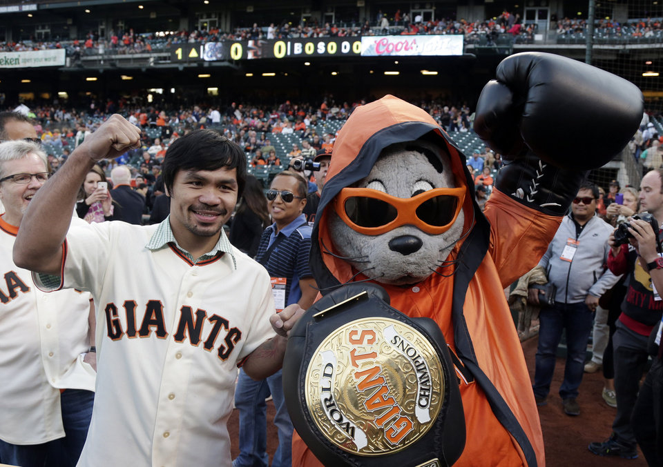 Photo - Boxer Manny Pacquiao, left, poses for pictures with San Francisco Giants mascot Lou Seal before Pacquiao was to throw the ceremonial first pitch before a baseball game between the Giants and Milwaukee Brewers on Friday, Aug. 29, 2014, in San Francisco. (AP Photo/Marcio Jose Sanchez)