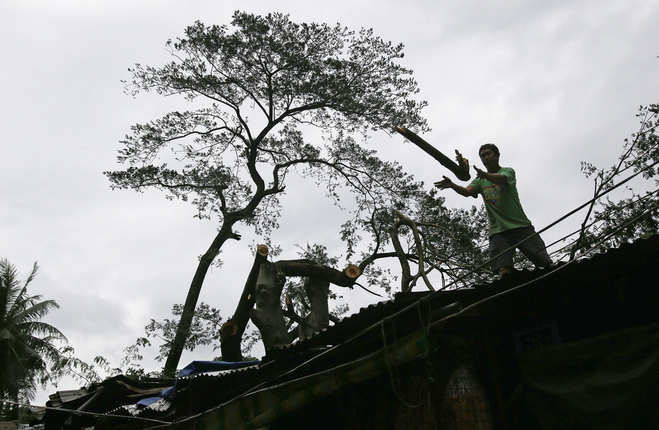 Photo - A worker removes sections of a fallen tree from a damaged house caused by Typhoon Koppu in suburban Quezon city, north of Manila, Philippines on Monday, Oct. 19, 2015. Army, police and civilian volunteers scrambled Monday to rescue hundreds of villagers trapped in flooded homes and on rooftops in a northern Philippine province battered by slow-moving Typhoon Koppu. (AP Photo/Aaron Favila)