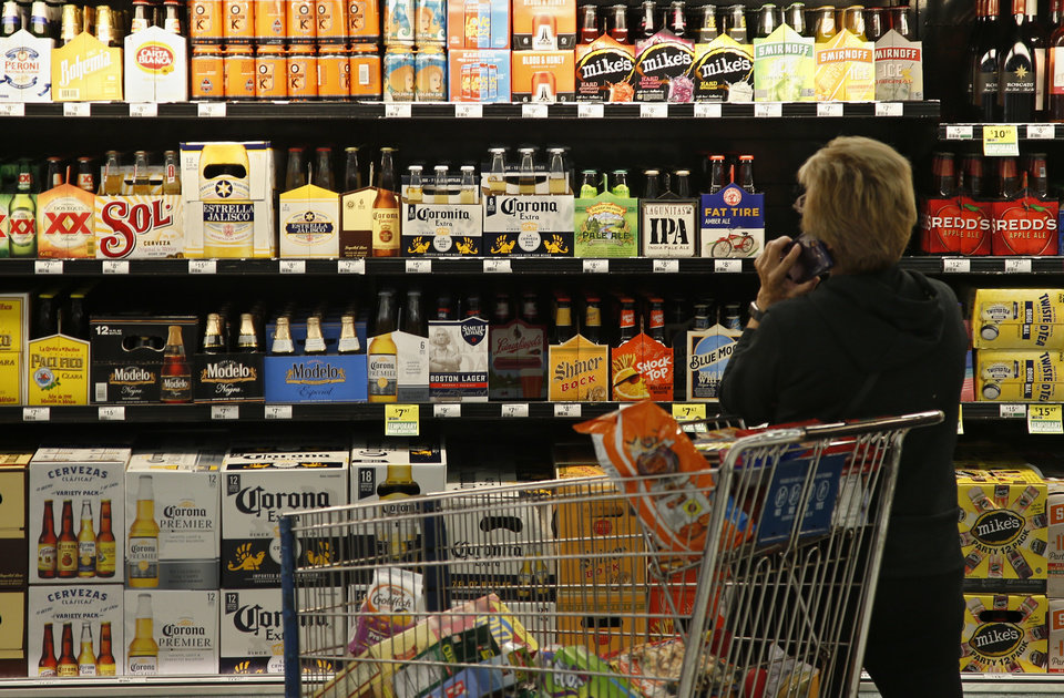 Photo -  A customer looks over the beer selection at Crest Foods in Oklahoma City on Oct. 1, the first day grocery stores and convenience stores in Oklahoma could legally sell wine and strong beer. [AP photo]