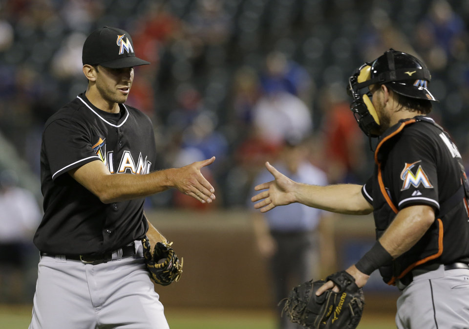 Photo - Miami Marlins closer Steve Cishek, left, is greeted by catcher Jeff Mathis after the final out of the baseball game against the Texas Rangers in Arlington, Texas, Tuesday, June 10, 2014. (AP Photo/LM Otero)
