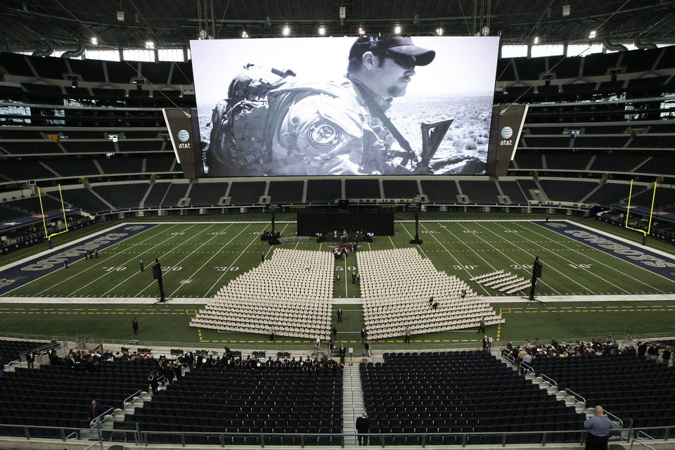 A photo of Christopher Kyle is displayed on the large screen before the start of a memorial service for the former Navy SEAL at Cowboys Stadium, Monday, Feb. 11, 2013, in Arlington, Texas. Thousands are expected to attend the public memorial service for Kyle, the former Navy SEAL sniper who was shot to death at a Texas shooting range. (AP Photo/Brandon Wade)