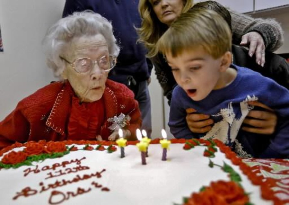 Ora E. Holland has help from great grandson Wade Davis to blow our her birthday candles as she has an early birthday celebration at Heritage Assisted Living Center on Saturday, Dec. 22, 2012, in Oklahoma City, Okla. Holland will celebrate her 112th birthday on Dec. 24, 2012. Photo by Chris Landsberger