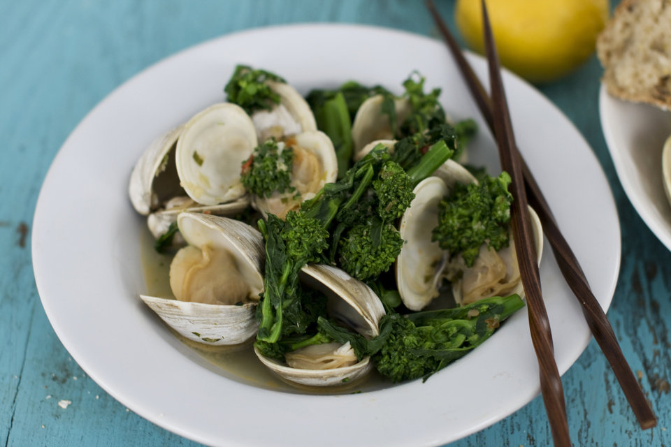 In this image taken on Feb. 11, 2013, Asian steamed clams or mussels with broccoli rabe is shown served in a bowl in Concord, N.H. (AP Photo/Matthew Mead)