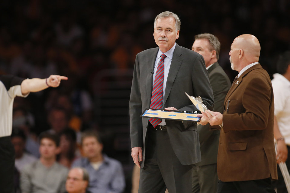 Photo - Los Angeles Lakers head coach Mike D'Antoni gets his clipboard from athletic trainer Gary Vitti during a time out against the Oklahoma City Thunder in the first half of an NBA basketball game in Los Angeles, Sunday, March 9, 2014. (AP Photo/Danny Moloshok)