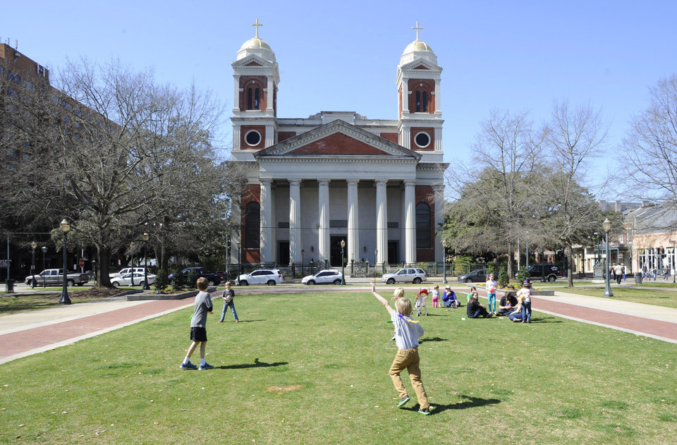 """Photo - Children play in a park near the Cathedral Basilica of the Immaculate Conception in Mobile, Ala., on Saturday, March 1, 2014. Mobile is that """"other"""" city on the northern Gulf Coast, the one that sometimes gets lost between the beaches of the Florida Panhandle and New Orleans. The church is among the free attractions in Mobile. (AP Photo/Jay Reeves)"""