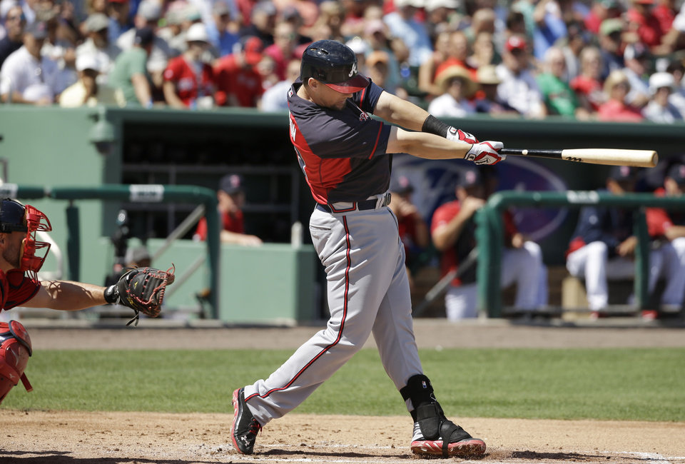 Photo - Atlanta Braves third baseman Chris Johnson, right, singles off a pitch by Boston Red Sox's Felix Doubront as Red Sox catcher David Ross, left, waits for the ball in the second inning of an exhibition baseball game Friday, March 7, 2014, in Fort, Myers, Fla. (AP Photo/Steven Senne)
