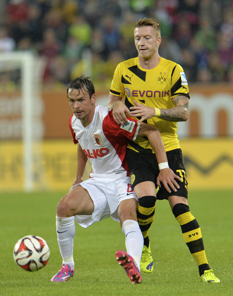 Photo - Augsburg's Markus Feulner, left, and Dortmund's Marco Reus challenge for the ball during their soccer match between FC Augsburg and Borussia Dortmund in the SLG Arena in Augsburg, Germany, on Friday, Aug. 29, 2014. (AP Photo/Kerstin Joensson)