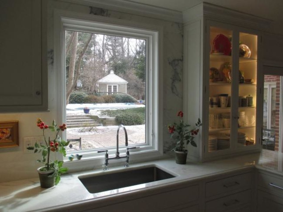 Photo -  The sink area in a Great Falls, Virginia, kitchen by designer Betsy Barmat Stires focuses on the view; she prefers to store dishwashing supplies under the counter. [BETSY BARMAT STIRES]
