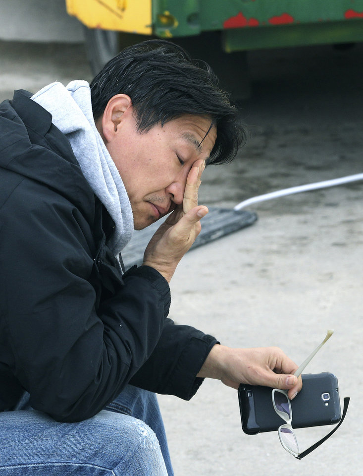 Photo - A relative of a passenger aboard the sunken Sewol ferry wipes his tears as he awaits news on his missing loved one at a port in Jindo, South Korea, Tuesday, April 22, 2014.  As divers continue to search the interior of the sunken ferry, the number of confirmed deaths has risen, with over 200 other people still missing. (AP Photo/Ahn Young-joon)