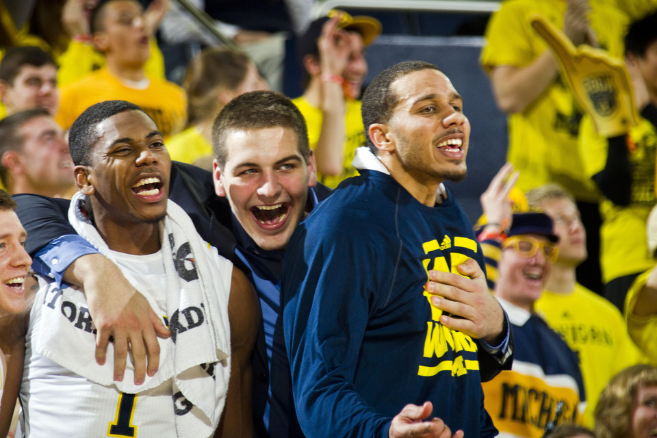 Photo - Michigan forward Mitch McGary, center, hugs and reacts with teammates Glenn Robinson III, left, and Jordan Morgan, right, from the bench in the first half of an NCAA college basketball game against Nebraska at Crisler Center in Ann Arbor, Mich., Wednesday, Feb. 5, 2014. (AP Photo/Tony Ding)