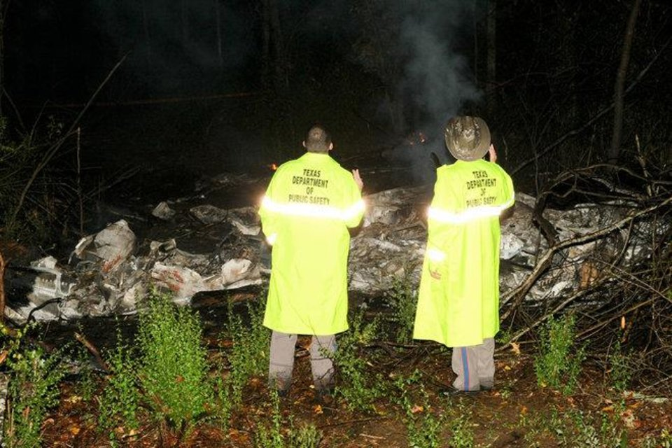 Texas Department of Public Safety Troopers Cody Sheperd (left) and David Hendry examine the smoky remains of a Cessna 421 that crashed in Cherokee County around 9:30 p.m. Monday. ANDY ADAMS/The Lufkin News