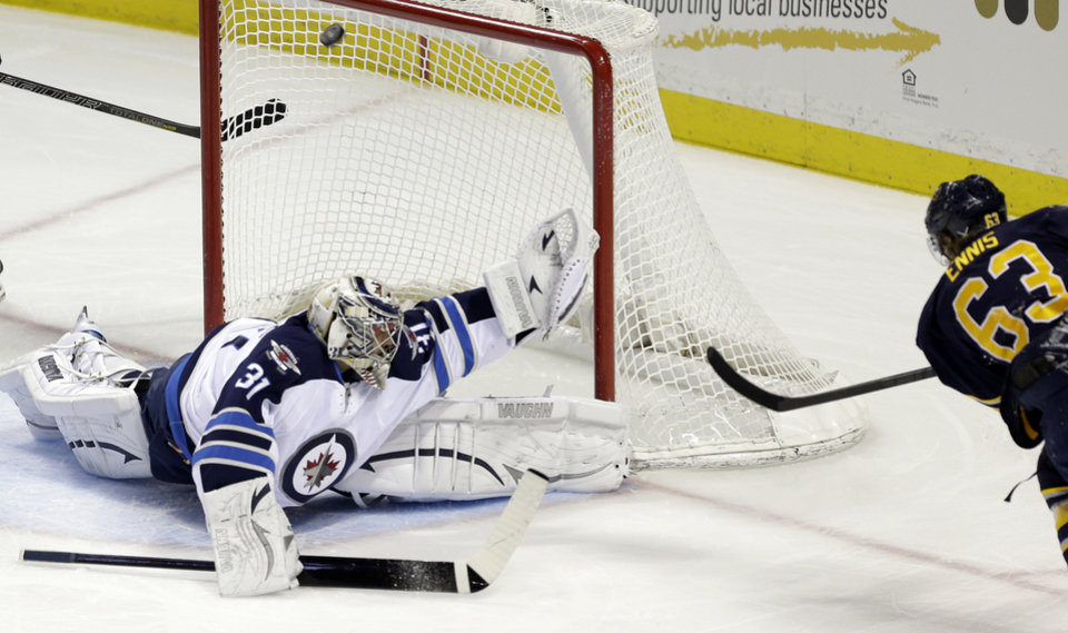 Photo - Buffalo Sabres' Tyler Ennis (63) shoots on Winnipeg Jets goalie Ondrej Pavelec, of Czech Republic, during the first period of an NHL hockey game in Buffalo, N.Y., Monday, April 22, 2013. (AP Photo/David Duprey)