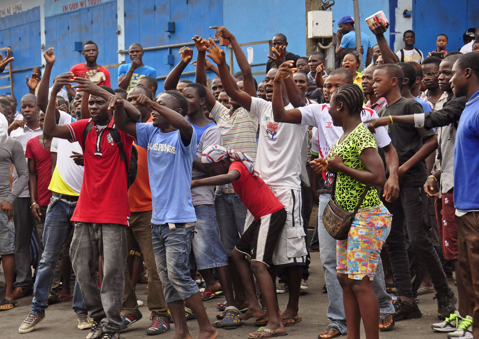 Photo - Residents from an area close to the West Point Ebola center, protest as they are not allowed to enter the area leading to their homes, after Liberia security forces blocked roads, as the government clamps down on the movement of people to prevent the spread of the Ebola virus in the city of Monrovia, Liberia, Wednesday, Aug. 20, 2014. Security forces deployed Wednesday to enforce a quarantine around a slum in the Liberian capital, stepping up the government's fight to stop the spread of Ebola and unnerving residents.(AP Photo/Abbas Dulleh)