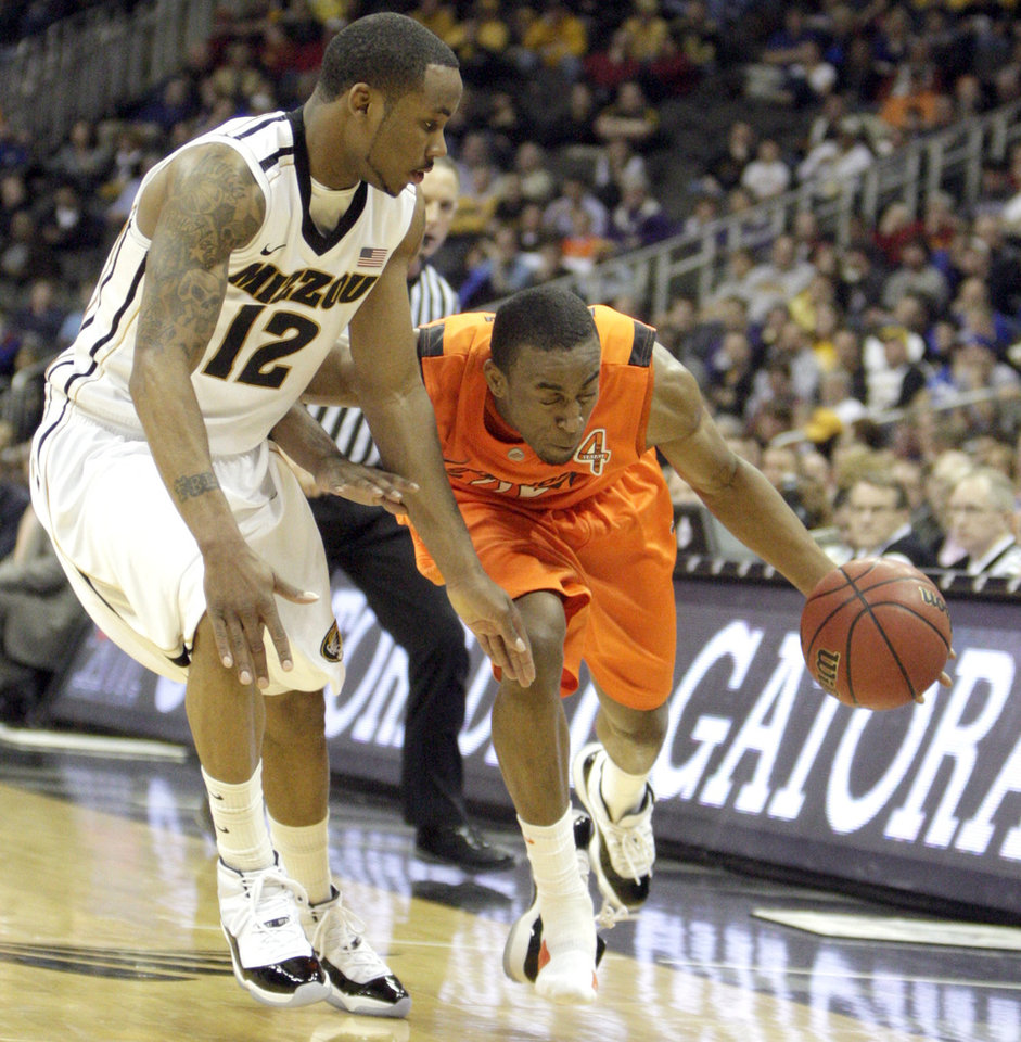Oklahoma's Markel Brown (22) tries to drive past Missouri's Marcus Denmon (12) during the Big 12 tournament men's basketball game between the Oklahoma State Cowboys and Missouri Tigers the Sprint Center, Thursday, March 8, 2012.  Photo by Sarah Phipps, The Oklahoman