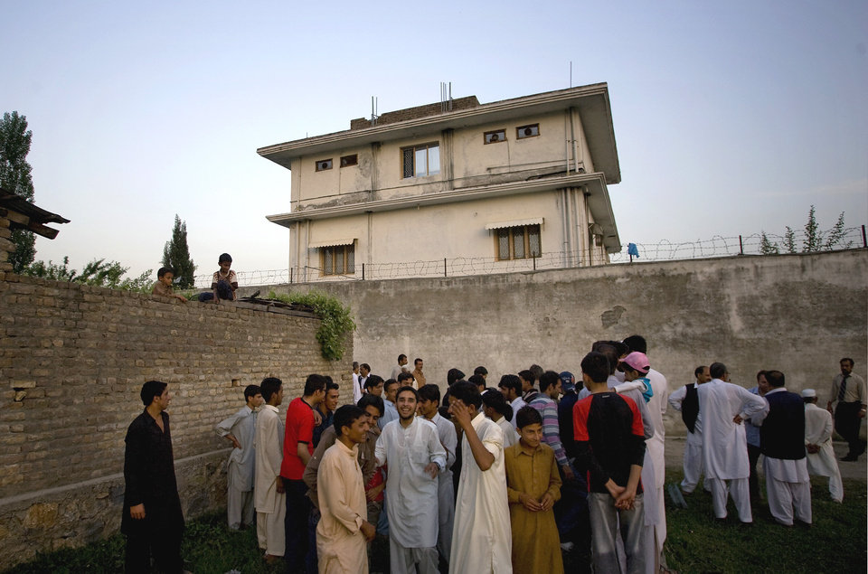 Photo -   FILE - In this May 3, 2011 file photo, local residents gather outside a house, where al-Qaida leader Osama bin Laden was caught and killed in Abbottabad, Pakistan. Local residents say Pakistan has started to demolish the compound in the northwest city of Abbottabad where Osama bin Laden lived for years and was killed by U.S. commandos. Two residents say the government brought in three mechanized backhoes Saturday, Feb. 25, 2012, and began destroying the tall outer walls of the compound after sunset. They set up floodlights to carry out the work. (AP Photo/B.K.Bangash,File)