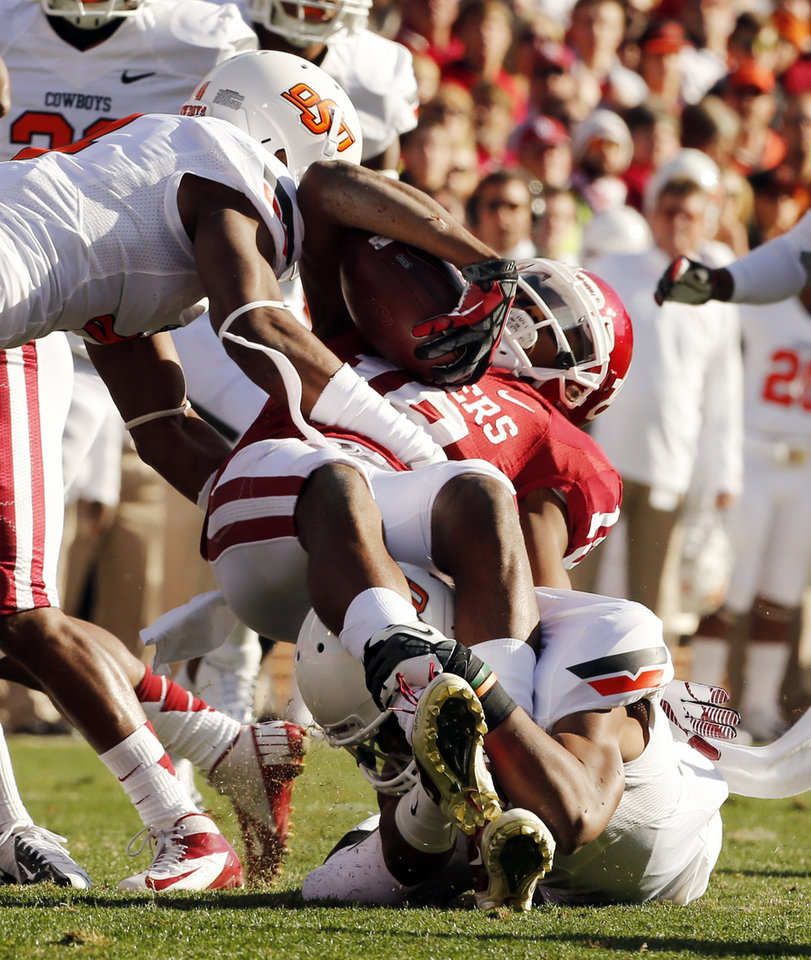 Photo - Oklahoma's Justin Brown (19) is brought down by Oklahoma State's Justin Gilbert (left) and Shamiel Gary (7) during the Bedlam college football game between the University of Oklahoma Sooners (OU) and the Oklahoma State University Cowboys (OSU) at Gaylord Family-Oklahoma Memorial Stadium in Norman, Okla., Saturday, Nov. 24, 2012. Photo by Steve Sisney, The Oklahoman