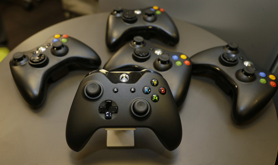 Photo - The new controller for Microsoft's next-generation Xbox One entertainment and gaming console system is shown front and center with older-generation controllers behind it, Tuesday, May 21, 2013, in Redmond, Wash. (AP Photo/Ted S. Warren)