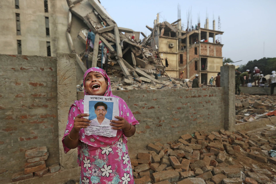 Photo - A Bangladeshi woman weeps as she holds a picture of her and her missing husband as she waits at the site of a building that collapsed Wednesday in Savar, near Dhaka, Bangladesh, Friday, April 26, 2013. The death toll reached hundreds of people as rescuers continued to search for injured and missing, after a huge section of an eight-story building that housed several garment factories splintered into a pile of concrete.(AP Photo/Kevin Frayer)