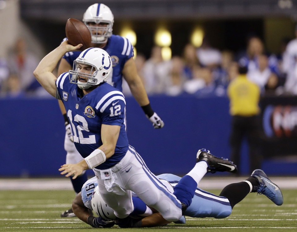 Photo - Indianapolis Colts quarterback Andrew Luck (12) throws an interception that was returned by Tennessee Titans' Will Witherspoon 40-yards for a touchdown as he is tackled by Derrick Morgan (91) during the first half of an NFL football game, Sunday, Dec. 9, 2012, in Indianapolis. (AP Photo/Jeff Roberson)