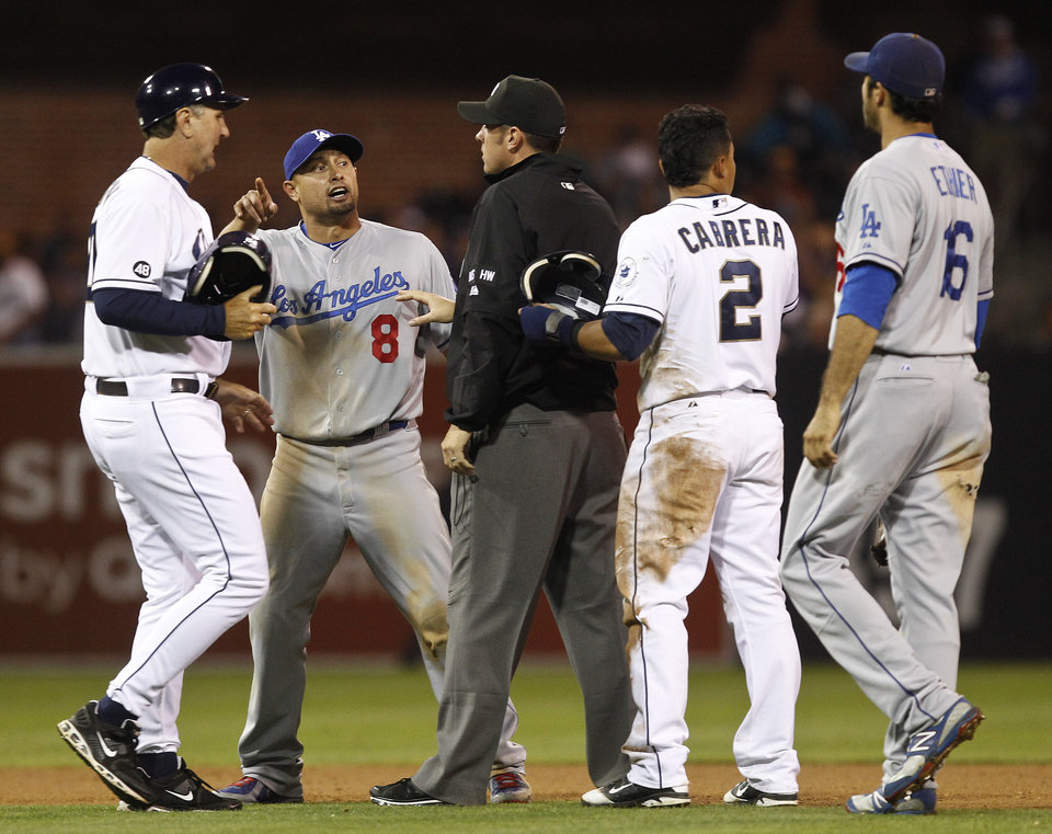 Photo -   Los Angeles Dodgers left fielder Shane Victorino is stopped by umpire Mark Ripperger as he tries to confront San Diego Padres' Everth Cabrera after Cabrera's slide into Dodgers second baseman Mark Ellis during the seventh inning of a baseball game Tuesday, Sept. 25, 2012 in San Diego. Padres coach Glenn Hoffman and Dodgers Andre Ethier arrive on the scene. (AP Photo/Lenny Ignelzi)