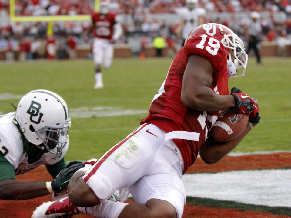 Photo - Oklahoma's Justin Brown (19) sores a touchdown in front of Baylor's Shawn Oakman (2) during the college football game between the University of Oklahoma Sooners (OU) and Baylor University Bears (BU) at Gaylord Family - Oklahoma Memorial Stadium on Saturday, Nov. 10, 2012, in Norman, Okla.  Photo by Chris Landsberger, The Oklahoman