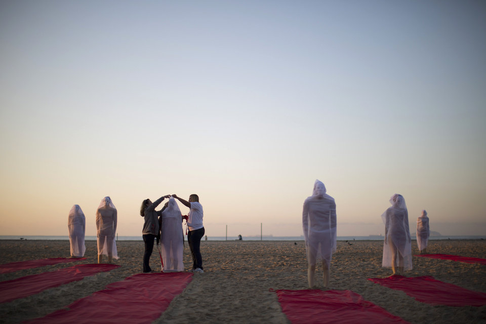 Photo - Rio de Paz activists wrap a mannequin in a veil during a protest on Copacabana beach to press for clarifications on missing persons including a bricklayer who recently disappeared, in Rio de Janeiro, Brazil, Wednesday, July 31, 2013. The 42-year-old father of six was picked up for police questioning on suspicions of involvement in drug trafficking, but was released shortly thereafter. He has not been seen since. Rio de Paz organization cites official statistics showing that nearly 35,000 people were reported as missing in Rio state alone over the past five years. (AP Photo/Felipe Dana)