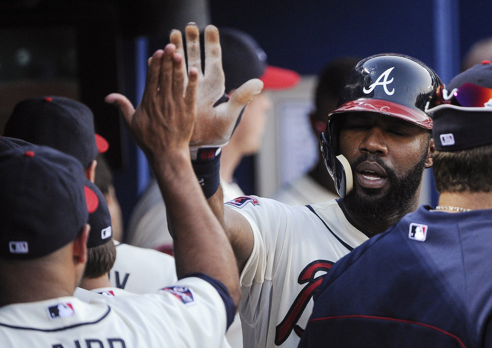 Photo - Atlanta Braves' Jason Heyward is congratulated in the dugout after scoring against the San Diego Padres on a single by Chris Johnson during the fourth inning of a baseball game, Saturday, July 26, 2014, in Atlanta. (AP Photo/John Amis)