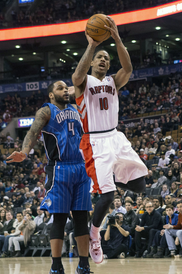 Photo - Toronto Raptors' DeMar DeRozan, right, shoots as Orlando Magic's Jameer Nelson defends during the first half of an NBA basketball game in Toronto, Sunday, Feb. 23 , 2014. (AP Photo/The Canadian Press, Chris Young)