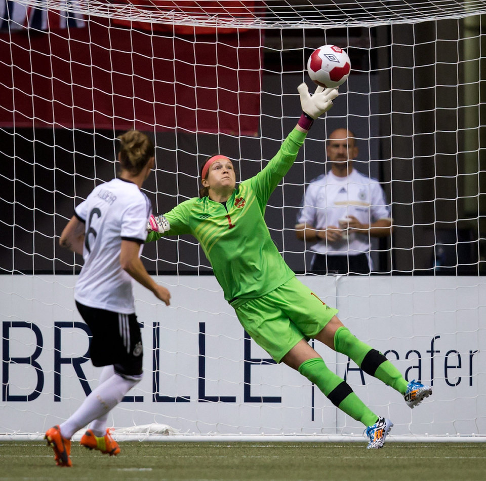 Photo - Germany's Simone Laudehr, left, scores against Canada's goalkeeper Erin McLeod on a penalty kick during the second half of an international women's soccer game in Vancouver, British Columbia on Wednesday, June 18, 2014.  (AP Photo/The Canadian Press, Darryl Dyck)