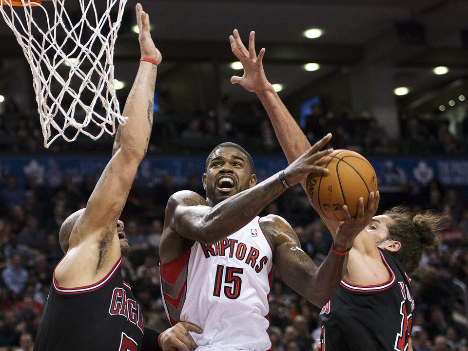 Toronto Raptors forward Amir Johnson (15) drives to the basket past Chicago Bulls' Carlos Boozer, left, and Joakim Noah during the first half of their NBA basketball game, Wednesday, Jan. 16, 2013, in Toronto. (AP Photo/The Canadian Press, Nathan Denette)