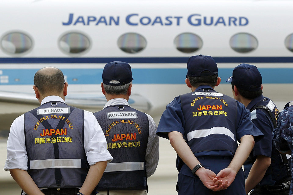 Photo - Members of the Japan Disaster Relief Team await the arrival of the Gulfstream 5 carrying members of the Japan Coast Guard at Pearce air force base on Wednesday, March 26, 2014, in Bullsbrook, Australia. The desperate, multinational hunt for Flight 370 resumed Wednesday across a remote stretch of the Indian Ocean after fierce winds and high waves that had forced a daylong halt eased considerably. A total of 12 planes and five ships from the United States, China, Japan, South Korea, Australia and New Zealand were participating in the search, hoping to find even a single piece of the Malaysia Airlines jet that could offer tangible evidence of a crash. (AP Photo/Will Russell, Pool)
