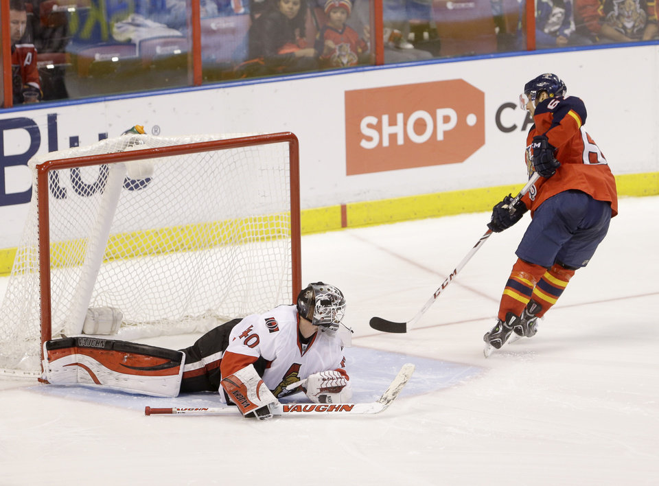 Photo - Florida Panthers center Vincent Trocheck scores against Ottawa Senators goalie Robin Lehner (40) during a shootout in an NHL hockey game, Tuesday, March 25, 2014 in Sunrise, Fla. The Panthers defeated the Senators 3-2. (AP Photo/Wilfredo Lee)