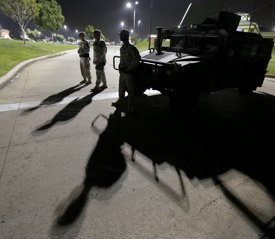 Photo - FILE - This Aug. 18, 2014 file photo shows members of the Missouri National Guard standing watch outside a command post near a protest for Michael Brown, who was killed by a police officer Aug. 9 in Ferguson, Mo. Brown's shooting has sparked more than a week of protests, riots and looting in the St. Louis suburb. Eric Holder, who is leading the federal response to the racial turmoil in Ferguson, Missouri, talks about the nation's civil rights struggles in a way none of the 81 previous U.S. attorneys general could _ by telling his own family story. (AP Photo/Charlie Riedel, File)