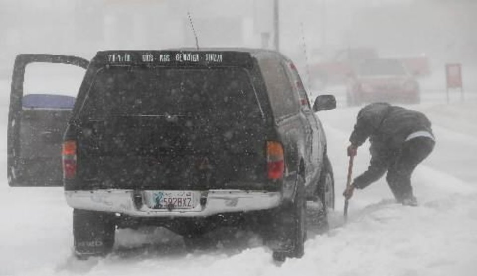 Photo -  Blizzard conditions in  Oklahoma City Thursday, Dec. 24, 2009. A man tries to dig his truck out of deep snow in a parking lot on Meridian. Photo by Jim Beckel