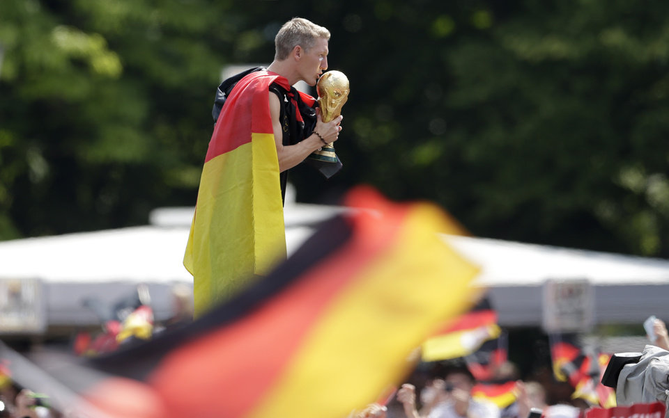 Photo - Bastian Schweinsteiger kisses the trophy during a fan party after the arrival of the German national soccer team in Berlin Tuesday, July 15, 2014. Germany beat Argentina 1-0 on Sunday to win its fourth World Cup title.  (AP Photo/Petr David Josek)
