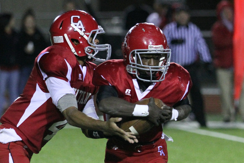 Photo - Carl Albert quarterback Dillan Dansby hands off to running back Darvonta Winston during the Carl Albert Titans - Ardmore Tigers football game Friday night at Jim Harris stadium in Midwest City. PHOTO BY HUGH SCOTT, FOR THE OKLAHOMAN