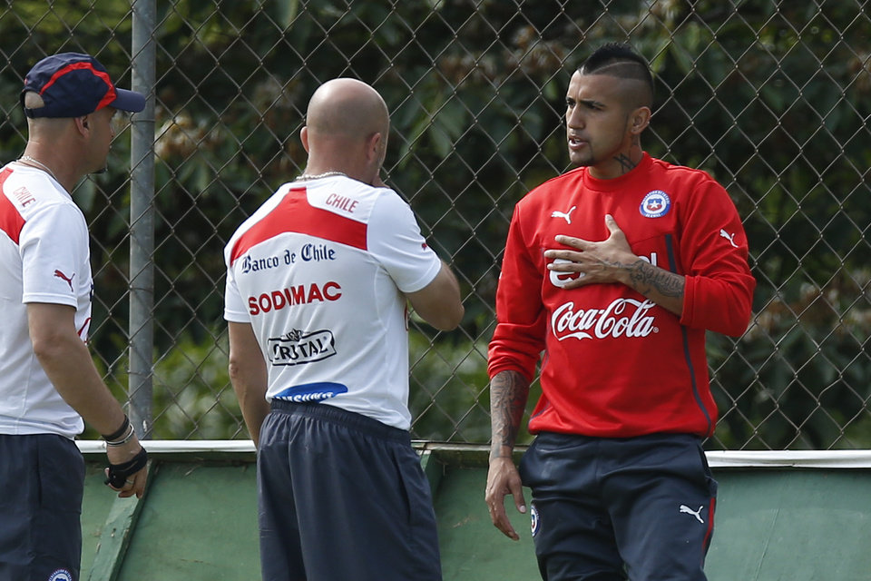 Photo - Chile's Arturo Vidal, right, talks with head coach Jorge Sampaoli, center, during a training session at Toca da Raposa 2 center in Belo Horizonte, Brazil, Thursday, June 19, 2014.  Chile plays in group B of the 2014 soccer World Cup. (AP Photo/Victor R. Caivano)