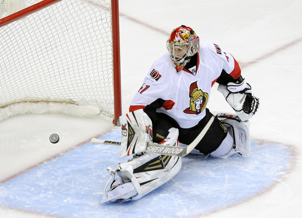 Photo - Ottawa Senators goalie Craig Anderson watches as the puck goes in the net on a goal by Colorado Avalanche left wing Jamie McGinn in the first period of an NHL hockey game on Wednesday, Jan. 8, 2014, in Denver. (AP Photo/Chris Schneider)