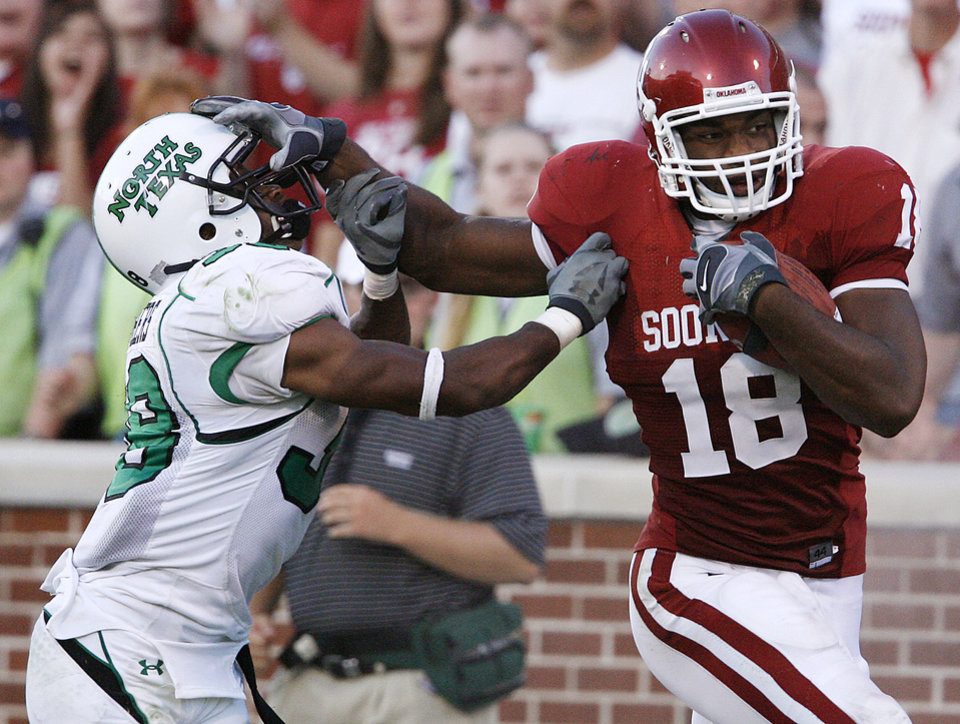Photo - Oklahoma's Jermaine Gresham (18) stiff arms North Texas' Bron Hager (39) in the first half during the University of Oklahoma Sooners (OU) college football game against the University of North Texas Mean Green (UNT) at the Gaylord Family -- Oklahoma Memorial Stadium, on Saturday, Sept. 1, 2007, in Norman, Okla.   By STEVE SISNEY, The Oklahoman  ORG XMIT: KOD