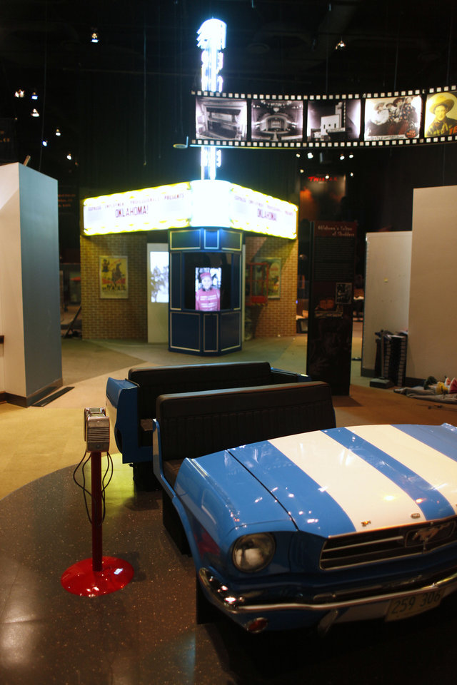 Photo - Visitors can sit in seats resembling a 1965 Mustang and watch a documentary on drive-in theaters in the drive-in display of the