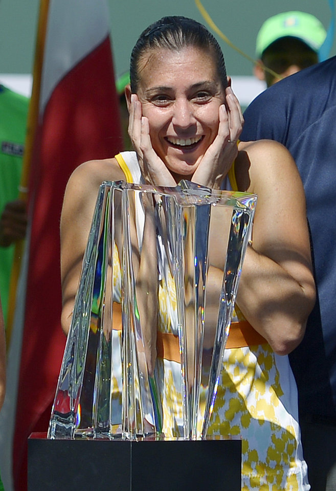 Photo - Flavia Pennetta, of Italy, reacts after being awarded the trophy after she beat Agnieszka Radwanska, of Poland, 6-2, 6-1, in the final round of the BNP Paribas Open tennis tournament, Sunday, March 16, 2014, in Indian Wells, Calif. (AP Photo/Mark J. Terrill)