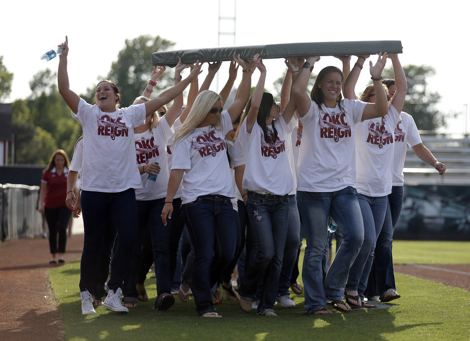 Photo - Oklahoma carry a section of the outfield wall at a celebration of their Women's College World Series title in Norman, Okla.,Friday, June 7, 2013. Photo by Sarah Phipps, The Oklahoman
