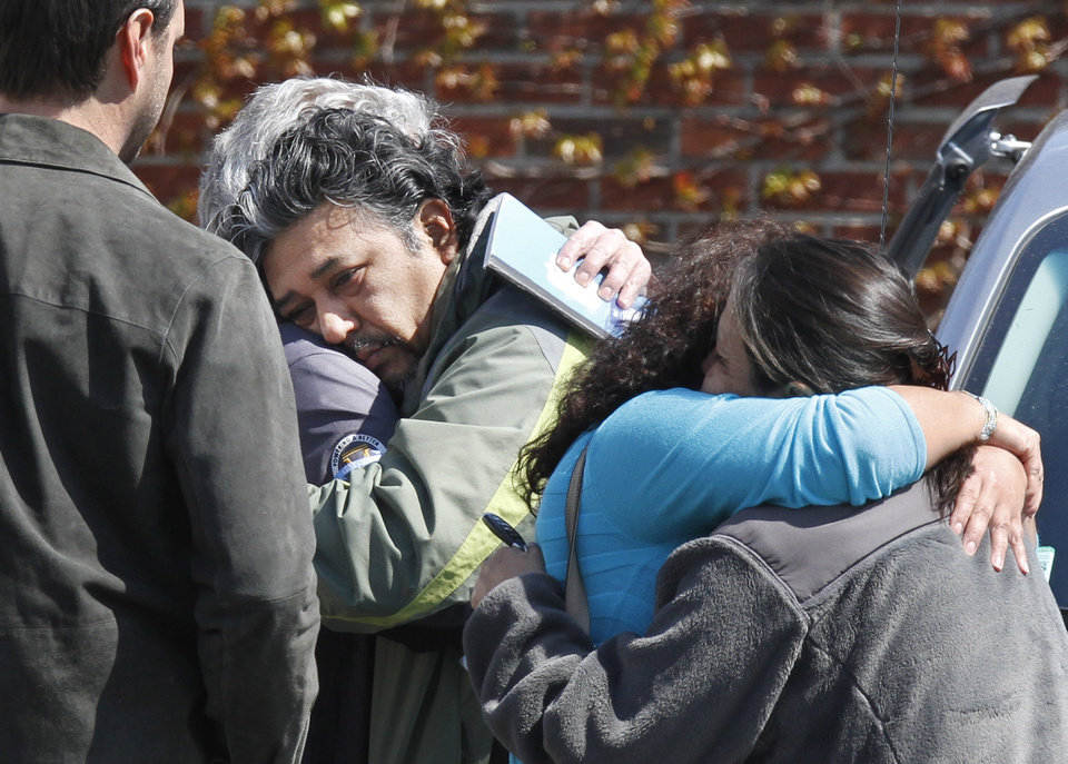 Photo -   Jose Garcia, center, is consoled after the body of his missing son, Boston College student Franco Garcia, was recovered at Chestnut Hill Reservoir in Boston, Wednesday, April 11, 2012. Franco Garcia disappeared Feb. 22 after leaving a popular bar near the college. (AP Photo/Michael Dwyer)