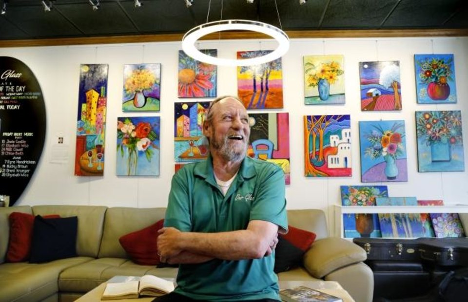 Photo -  Doug Lott is manager of Our Glass, one of El Reno's newest restaurants. Lott is shown Wednesday in front of a wall featuring pieces by local artists. [Jim Beckel/The Oklahoman]